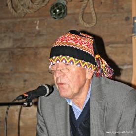 Nils Harald imiterer ein informant som lærte han Lønosongen. Brillene og strikkaluo frå Fjell på plass, og song med skjelvande stemme